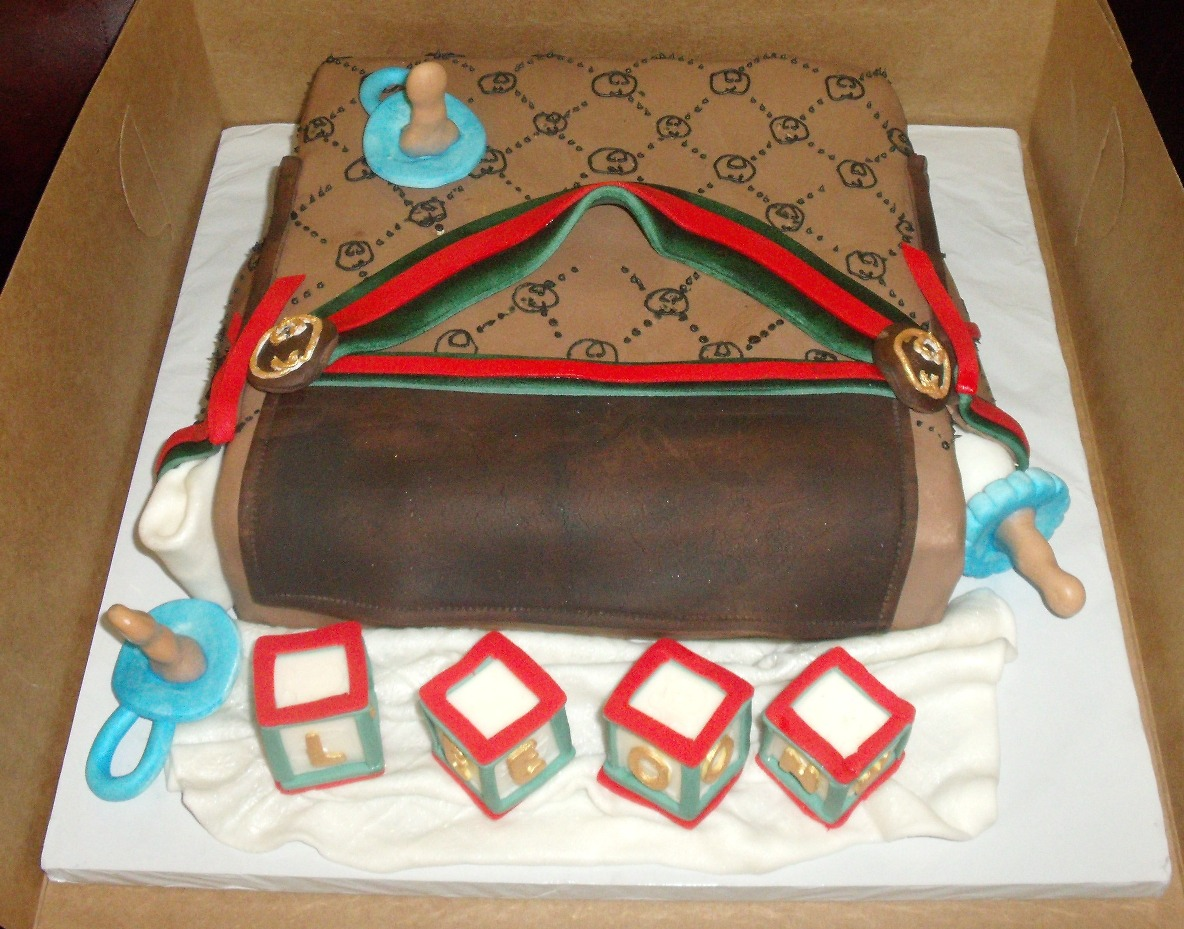 Gucci Baby Diaper Bag Cake With Edible Baby Blocks, Pacifiers, Baby Bottle top view